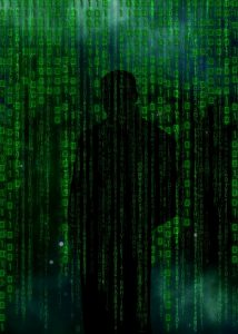 man standing veiled by binary codes in green and black