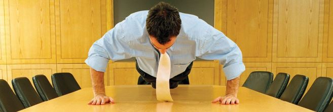 business-man-doing-pushups-on-conference-table