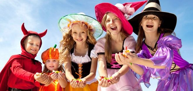 kids-in-halloween-costumes-holding-candy-in-front-of-blue-sky
