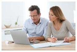 man-and-woman-working-on-laptop-and-paper