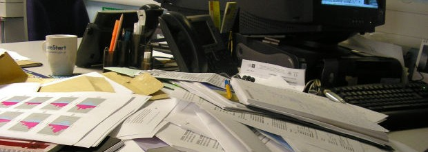 messy-desk-covered-wtih-papers-phone-computer